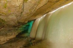 Med is grotta bak vattenfallet Arkivbild
