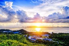 By med härlig solnedgång över den Hong Kong kustlinjen Arkivfoto