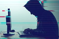 Med huva datoren hacker som arbetar på datoren för skrivbords- PC Royaltyfri Foto