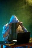 Med huva datoren hacker som stjäler information med bärbara datorn Royaltyfri Bild