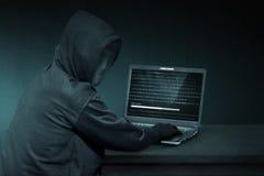 Med huva en hacker med den anonyma maskeringen genom att använda bärbara datorn för att stjäla data royaltyfria bilder