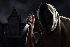 Med huva man i maskering med en kniv Royaltyfri Foto