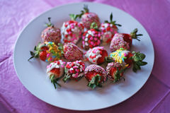 Med is jordgubbar som doppas i mångfärgade fester Royaltyfri Foto