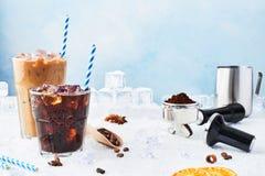 Med is kaffe för sommardrink i ett exponeringsglas- och iskaffe med kräm i ett högväxt exponeringsglas som omges av is Barista be royaltyfri fotografi