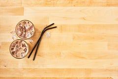 Med is kaffe i högväxt exponeringsglas med svarta metallsugrör royaltyfri bild