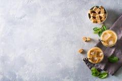 Med is kaffe i högväxta exponeringsglas med kräm och stycken av socker, mintkaramell Royaltyfri Bild