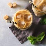 Med is kaffe i högväxta exponeringsglas med kräm och stycken av socker, mintkaramell Fotografering för Bildbyråer