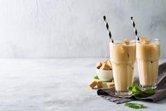 Med is kaffe i högväxta exponeringsglas med kräm och stycken av socker, mintkaramell Royaltyfri Foto