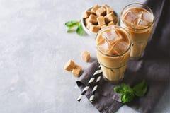 Med is kaffe i högväxta exponeringsglas med kräm och stycken av socker, mintkaramell Arkivbilder