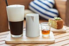 Med is kaffe med mjölkar och täcker med sirap Arkivbilder