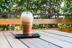 Med is kaffe och smartphone på trätabellen Royaltyfri Bild