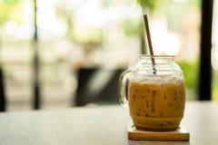 Med is kaffe med röret på tabellen på kafét arkivfoton