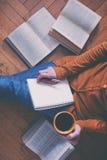 Med kaffekoppen efter läseböcker arkivfoton
