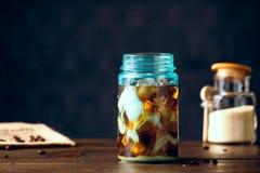 Med is kallt organiskt strikt vegetariankaffe med mjölkar virvlar i blåa Mason Jar arkivfoto