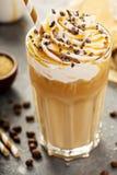 Med is karamelllattekaffe i ett högväxt exponeringsglas Arkivbild