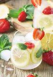 Med is lemonad för sommar med jordgubbar, citronen, mintkaramellen och sodavatten, wood bakgrund för tappning, selektiv fokus arkivfoton