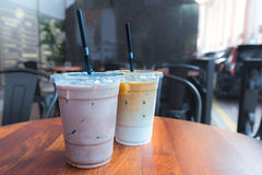 Med is mocka och med is Lattekaffedrinkar i klara plast-koppwi Royaltyfria Bilder