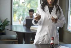 Med School Student and Female Scientist. Female scientist in a lab coat researching with her male coed med school student in a campus laboratory.  The women is Royalty Free Stock Photos