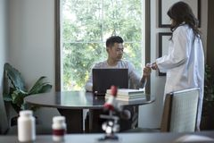 Med School Student and Female Scientist. Female scientist in a lab coat researching with her male coed med school student in a campus laboratory.  The women is Royalty Free Stock Photo