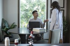 Med School Student and Female Scientist. Female scientist in a lab coat researching with her male coed med school student in a campus laboratory.  The women is Stock Photos