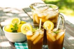 Med is te med citronen och mintkaramellen på picknicktabellen Royaltyfri Fotografi