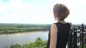 MED Young-wijfje die neer op een meer vanaf de bovenkant van berg kijken stock footage