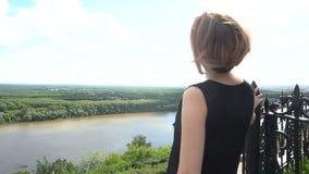 MED Youngs-Frau, die unten auf einem See von der Spitze des Berges schaut stock footage
