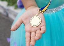 Medaglia d'oro alla mano della ragazza Laureato dal giardino più gentile fotografia stock