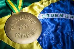 Medaglia d'oro di Olympics di Rio 2016 sulla bandiera del Brasile Fotografia Stock