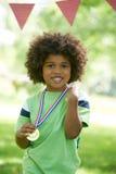 Medaglia di conquista del giovane ragazzo alla giornata di gare sportive Immagini Stock