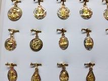 medaglie d'oro con le immagini religiose nei gioielli fotografia stock