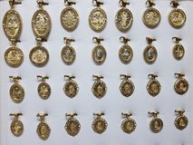 medaglie d'oro con le immagini religiose nei gioielli fotografia stock libera da diritti