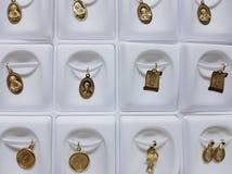 medaglie d'oro con le immagini religiose nei gioielli immagini stock libere da diritti