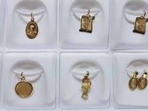 medaglie d'oro con le immagini religiose nei gioielli fotografie stock