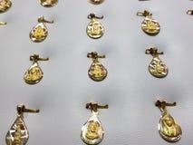 medaglie d'oro con le immagini religiose nei gioielli immagine stock