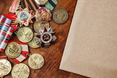 Medaglie dell'URSS e dei meriti degli anni differenti e carta su una tavola Immagine del fuoco selettivo Fotografia Stock Libera da Diritti