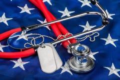 Medagliette per cani e stetoscopio in bianco sulla bandiera americana fotografia stock libera da diritti