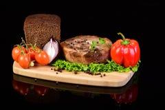Medaglione della carne con le verdure su un tagliere di legno Immagini Stock Libere da Diritti