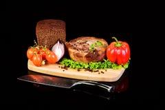 Medaglione e verdure della carne su un bordo di pane Fotografia Stock