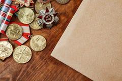 Medaillen der UDSSR und der Verdienste der verschiedenen Jahre und Papier auf einer Tabelle Lizenzfreie Stockfotos