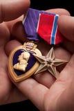 Medailles van de Oorlog van het Hart en van het Brons van de Holding van de mens de Purpere stock afbeeldingen