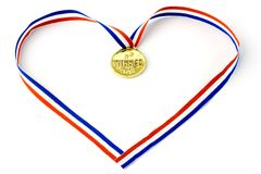 Medal. Red, white and blue ribbon hold a gold medal.Heart shape. Isolated Stock Photo