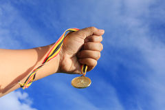 Medal and hand. Hand holding gold medal on blue sky Stock Photos