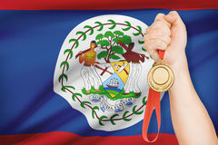Medal in hand with flag on background - Belize. Sportsman holding gold medal with flag on background Stock Photo