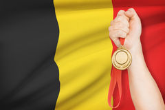 Medal in hand with flag on background - Kingdom of Belgium Royalty Free Stock Images