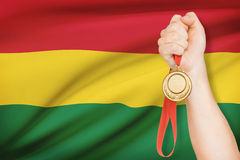 Medal in hand with flag on background - Plurinational State of Bolivia. Sportsman holding gold medal with flag on background - Plurinational State of Bolivia Stock Photos