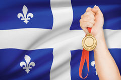 Medal in hand with flag on background - Quebec. Sportsman holding gold medal with flag on background - Quebec Royalty Free Stock Photos