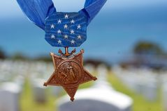 Medal of Honor. Congressional Medal of Honor hanging in the air with a military cemetery in the background Stock Photos