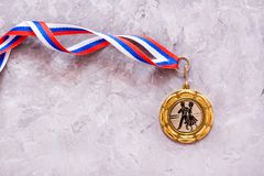 Medal with the image of dancers on a tape on a gray background. Medal with the image of dancers on a tape on a gray non-uniform background. Top view Stock Image