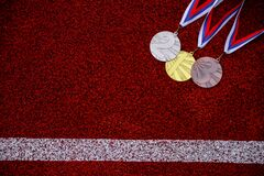 Medal set at red athletics track, Victory, sport success concept photo, Red edit space